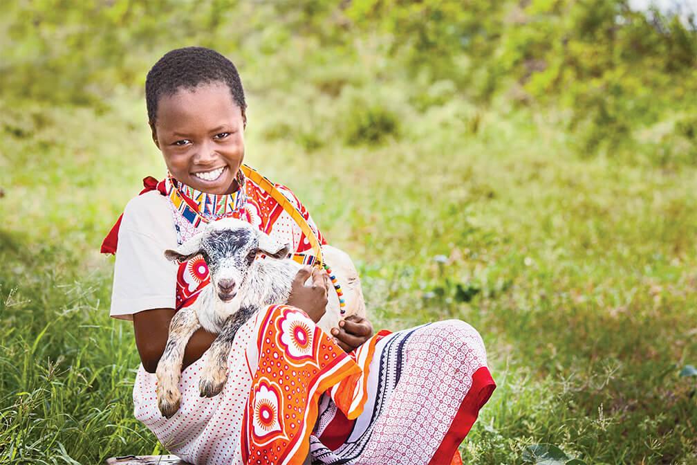 Benson, age 8, with a goat in Mashuru ADP.